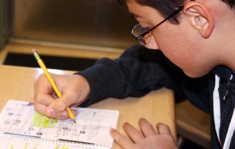 Mackenzie Herren manages his schedule by writing his homework in his planner on Oct. 26. Photo by SARAH HENSCHEL