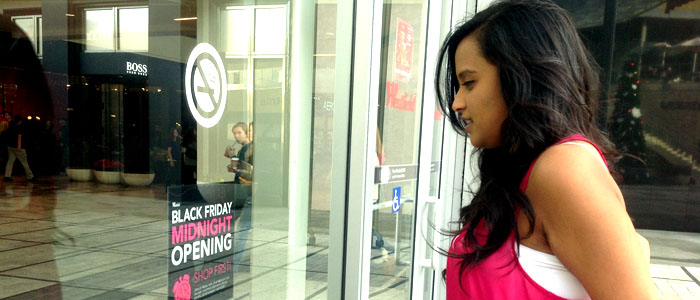Senior Joyee Mallick looks at a Black Friday poster at the Westfield Galleria Mall on Nov. 21. Photo by KAVYA PATHAK.