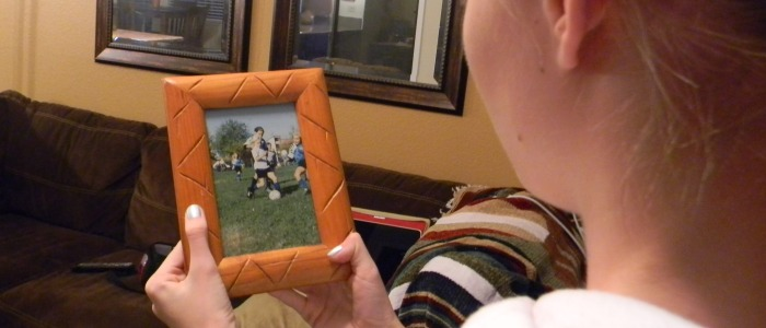 Shai Nielson looking at an old photograph of her playing soccer when she was younger. Photo by SHANNON NIELSON