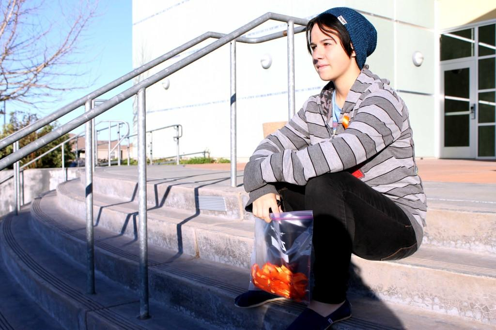 Meg Harper sits outside the theater to pass out orange ribbons on Mar. 1 in support of Self-Harm Awareness day and to bring awareness to SKATE club. Photo by EMMA RICHIE