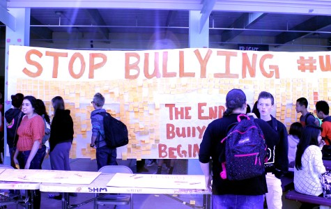 Students look at the poster filled with others' bullying stories. Photo by Abi Brooks on Oct. 9.