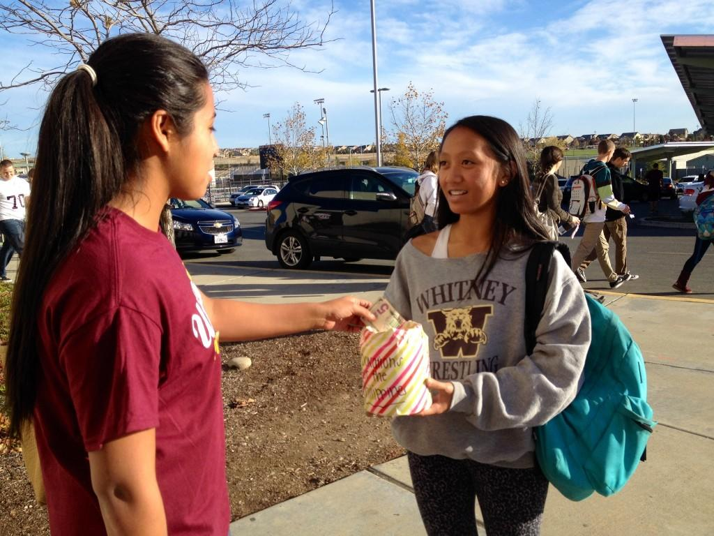 Kristen El Sayegh catches up with club president Sarah Martinez to donate money on Nov. 22. Photo by OLIVIA GRAHL