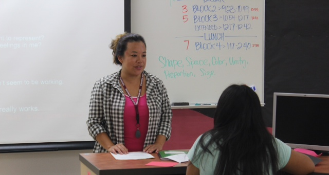 Ms. Whitney Lum helps her students with their projects in class. Photo by Abi Brooks.