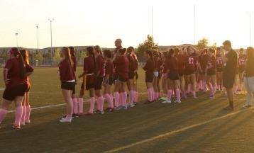 Sophomore girls line up along the sidelines of the football field in preparation for the game.