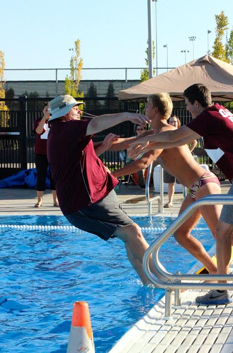 Matt Judy and Connor Miersch push Mr. Knowles into the pool; photo by Sierra Young