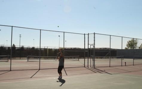 Freshman Keiko Watari throws the ball in the air ready to hit a slice serve. Photo by Missie Caracut