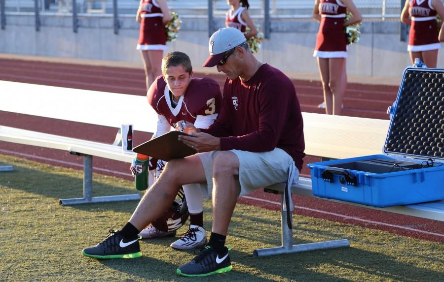 Head coach Mike Gimenez helps a JV football player with the plays. Photo by Sierra Young