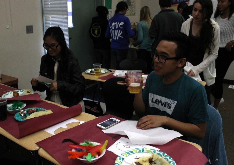 Students enjoy traditional Mardi Gras foods while creating colorful masks.