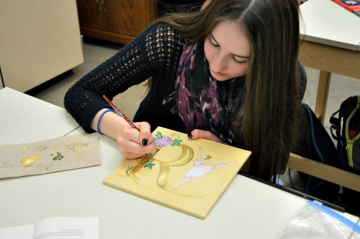 Roberta Romans works on tea stained paper to create her illuminated letter.