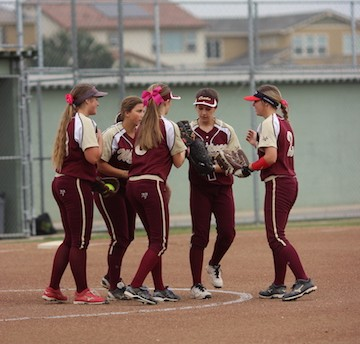 The team meets at the pitcher's mound to talk about plays. Photo by Makenna Schroeder