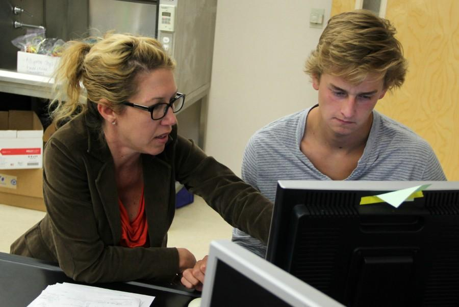 Mrs. Stephanie Ireland works with a student on their homework assignment.
