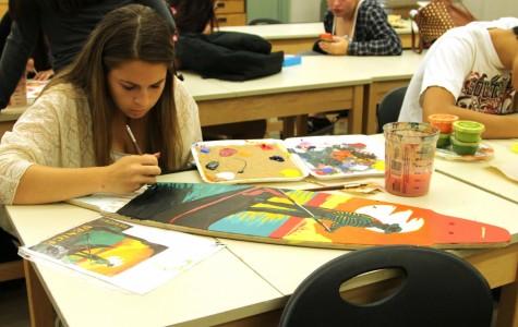 Art II paints skateboards with acrylic paint
