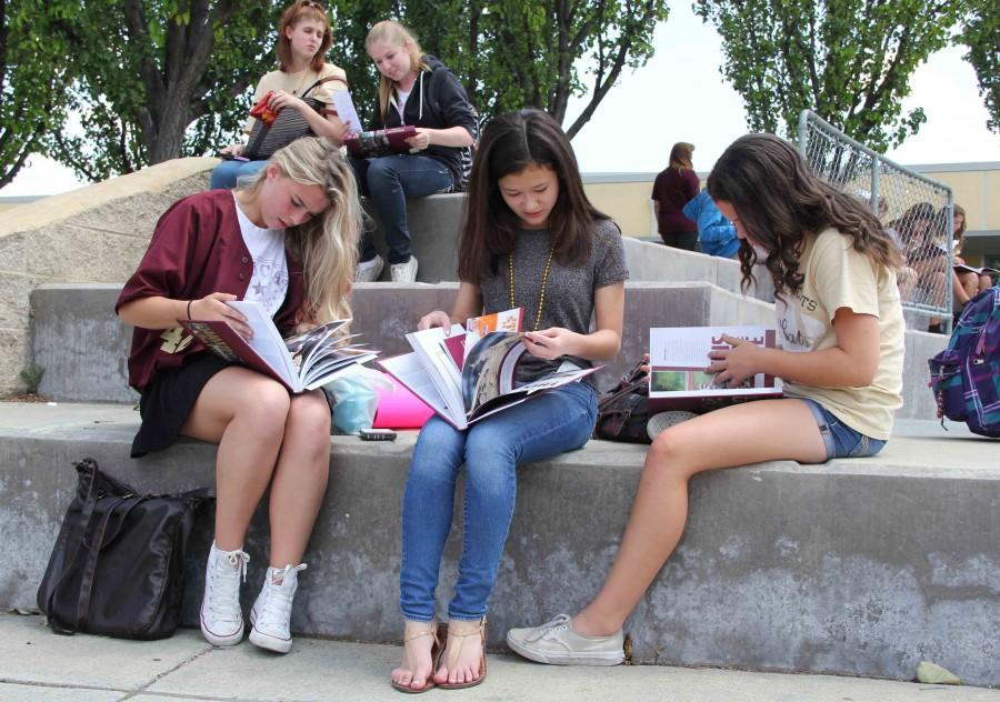 Braydin Prevo, Ashley Shirhall and Michaela Puleo  look through their yearbooks at the signing party on May 22. Photo by Annessa DeSouza