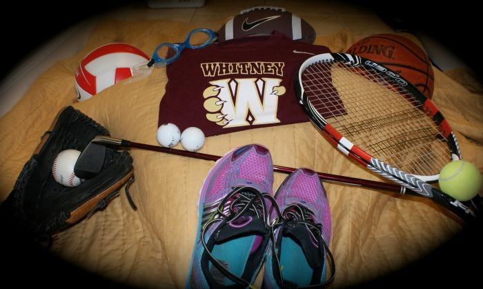 Equipment from school sports are shown surrounding a wildcat t-shirt. Photo by Daniel Sharrah
