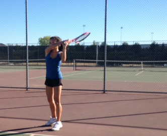 Women's varsity tennis player uses two handed-forehand