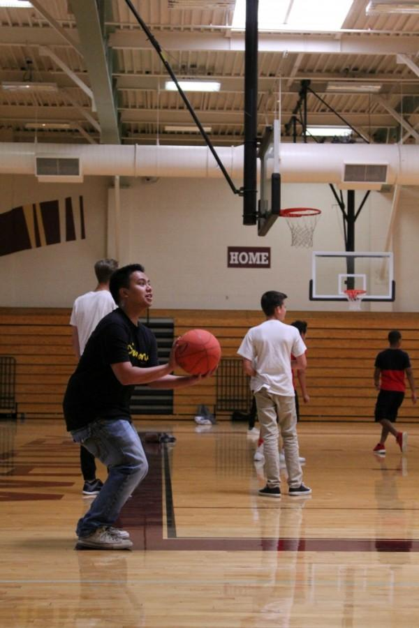 Elmo Canlas shoots a basketball during team sports.