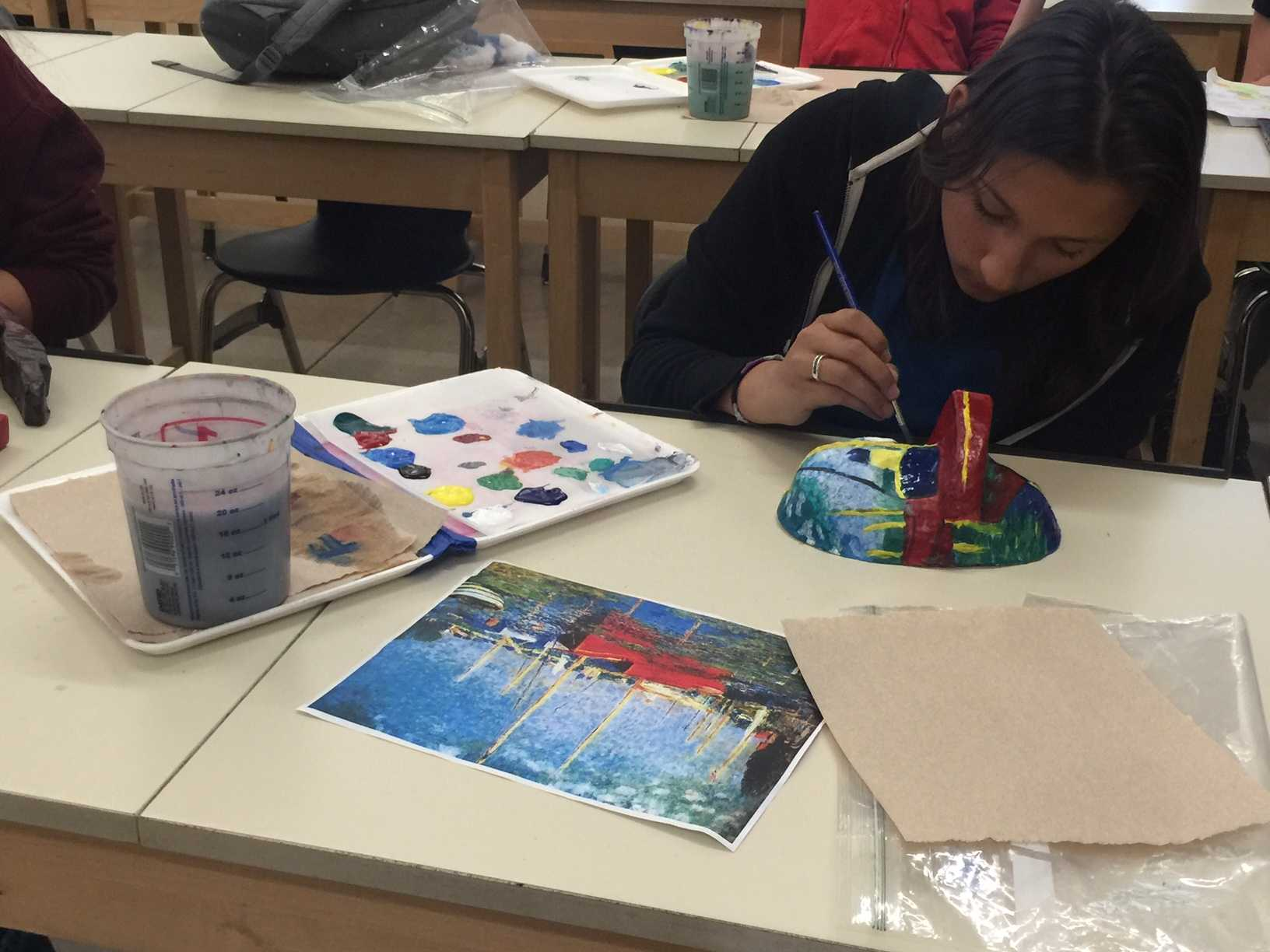 Students use paints to replicate a painting onto a 3D mask. Photo by Rachel Marquardt