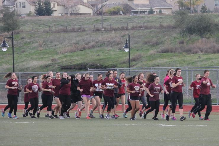 The girls planning on trying out for the softball team warm up for conditioning with laps around the football field.  Photo by Avery Van der Linden