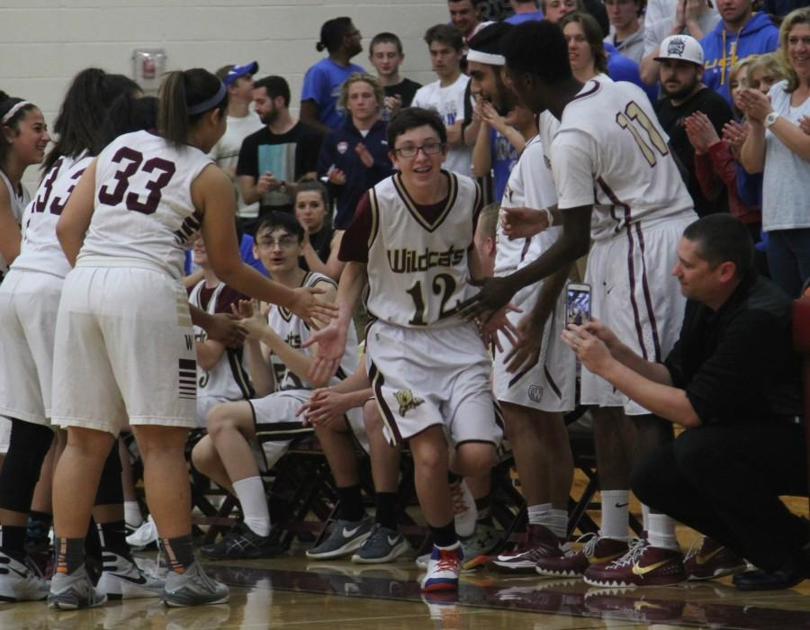Caden Evans high-fives teammates as his name is announced before the game. Photo by Deanna Payan.