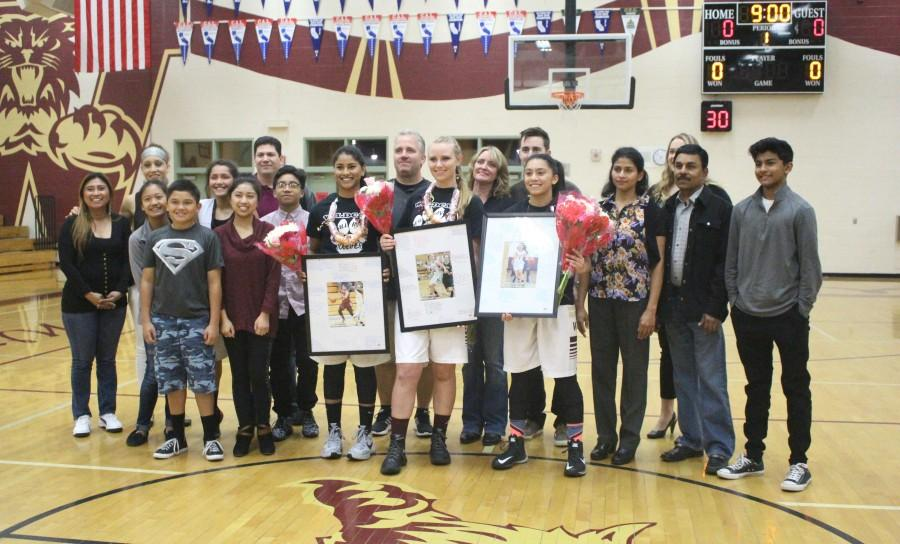 Seniors Maria Sabu, Lauren Roskelley and Dominique Bustamante pose with their families and gifts during the ceremony before the game. Photo by Rylea Gillis.