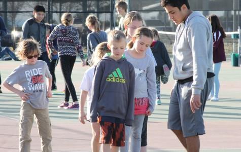 Varsity tennis teams host children's tennis camp