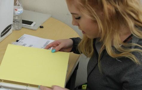 Savannah Austin puts together binders for the new senior mentors. Photo by Rachel Larson