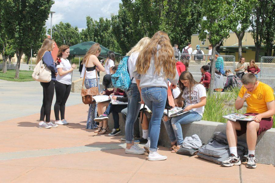Students sit around the small amphitheater to view and sign yearbooks on May 20. Photo by Kayla Hung