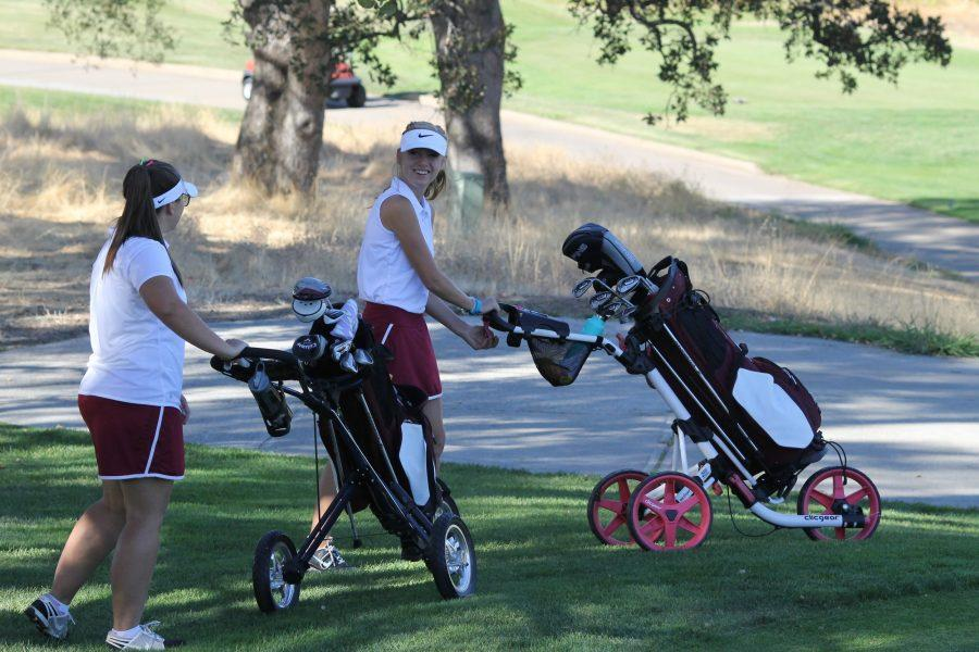 Varsity players Emily Hodgson and Eva Lopes talk and prepare for tee off against Cosumnes Oaks. Photo by Ella Ho Ching.