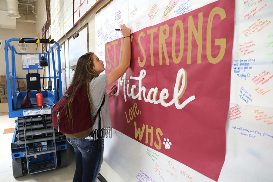 Brynn Blatnick signs the poster for Micheal Klaman during lunch on Oct. 26. Photo by Rachel Marquardt