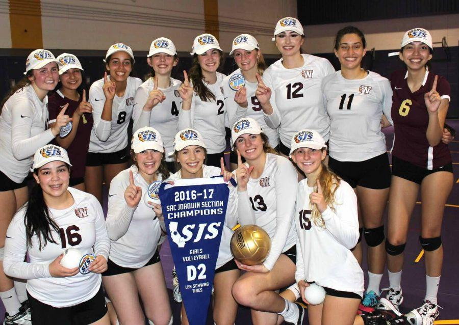 After receiving their championship hats and banners, the women's volleyball team poses for a team photo, holding up the number one.