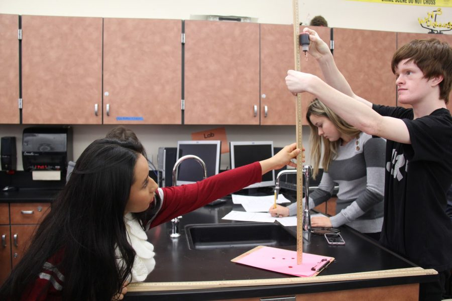 For a lab in forensics, Dianna Duran and Lucas Thurman test the different splatters blood makes when dripped from varying heights. Photo by Mikayla Ayala