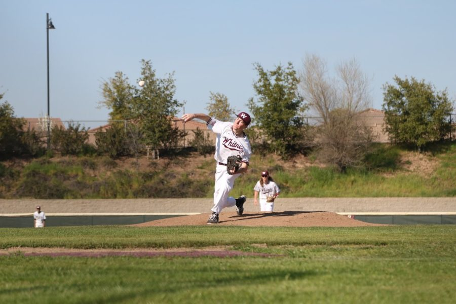 At the men's varsity baseball game against Bella Vista March 14, John Crouse throws his last pitch during warm-ups for a throwdown. Photo by Morgan Hawkins.