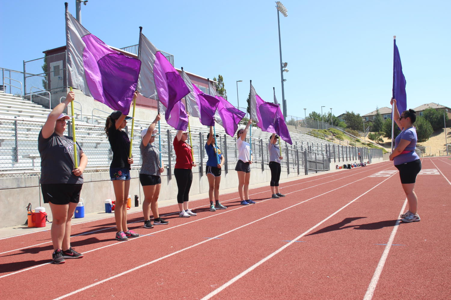 Color+guard+members+practice+movements+with+their+flags+on+the+track+at+band+camp+Aug.+9.+Photo+by+Danica+Tran.+