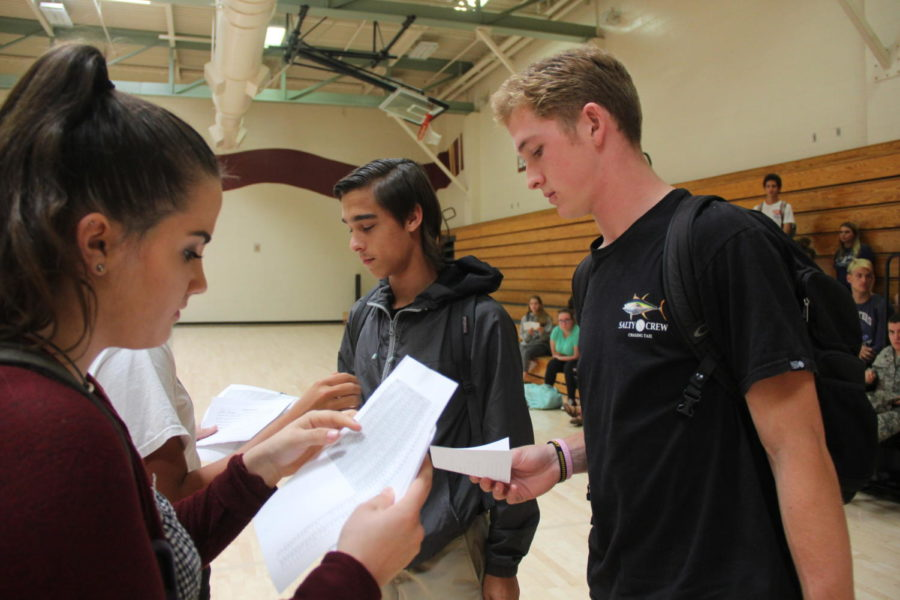 At the Breaking Down the Walls group leader meeting Oct. 25, Marissa Lewis gives Cole Kachmar and Robert Jones the days they will be participating and an information sheet. Photo by Cameryn Oakes