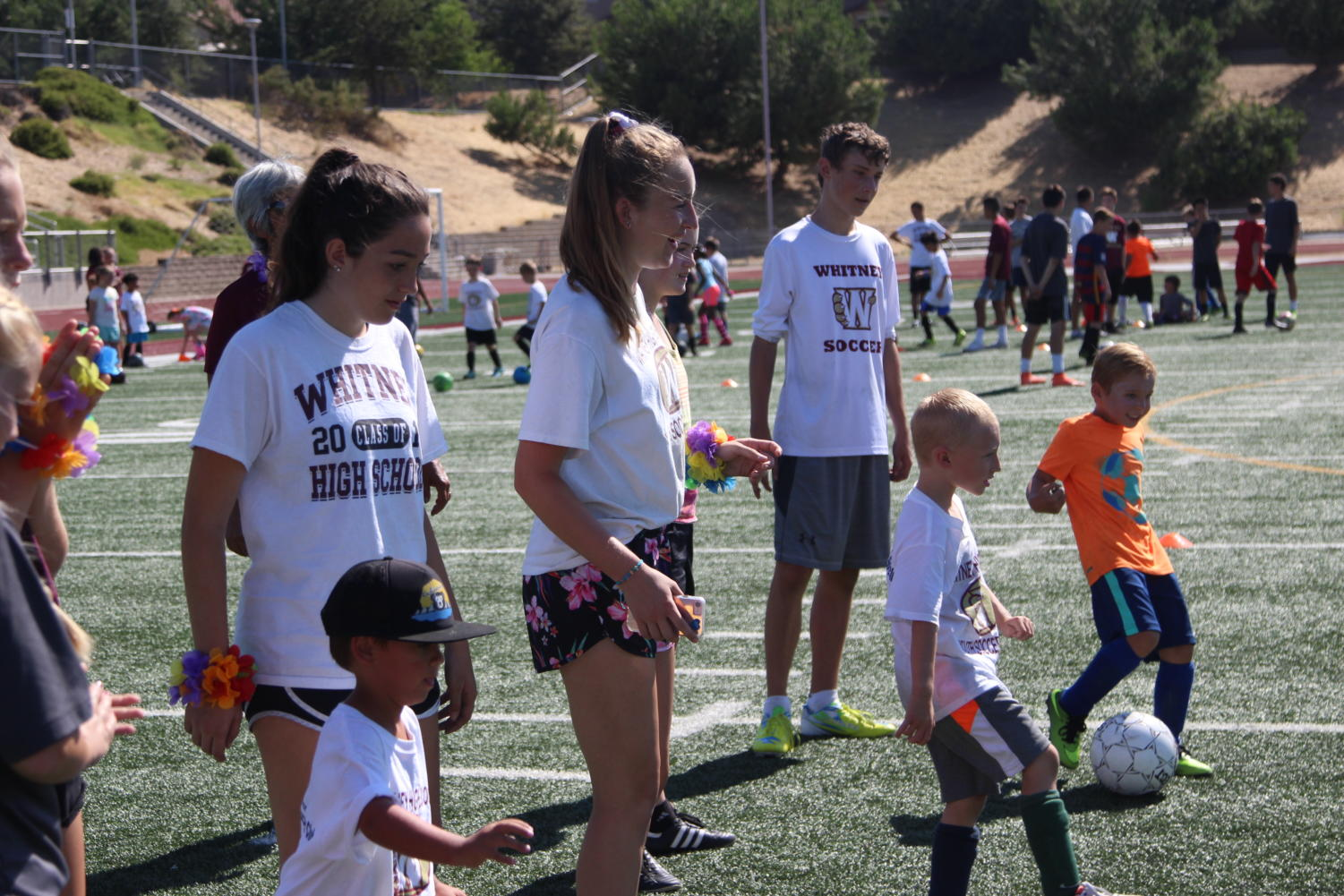 During the Whitney Kids Camp on July 24, Maddy Cortez, Mikayla Barkve and Connor Hedman practice passing with the participants. Photo by Britney Flint.