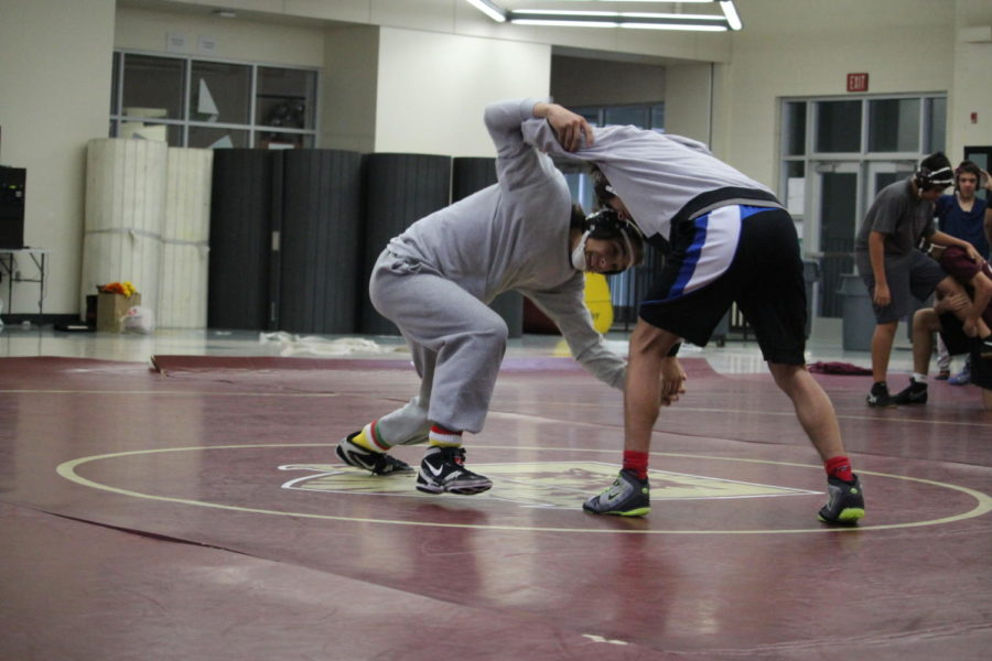 During practice in the cafeteria Nov. 20, Cole and Joe Kachmar work on takedowns. Photo by EmC Cowles.