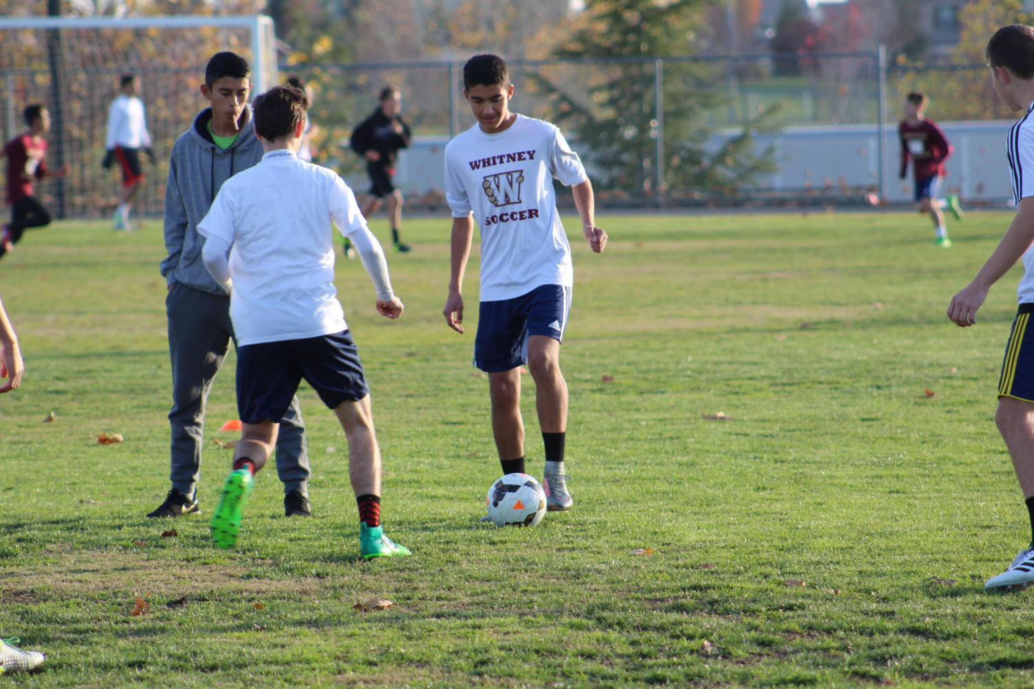 As a part of a keep away-drill used to improve passing skills, Miguel Saavedra dribbles around Nate Sherwood during practice Dec. 18. Photo by Blake Wong.