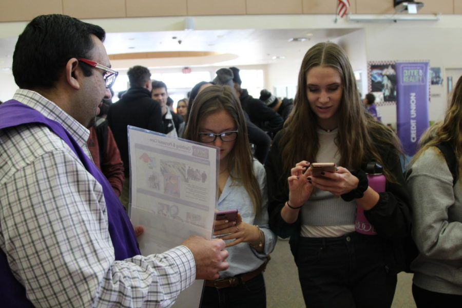 At the Bite of Reality simulation, Megan Soares and Meghan Townsley, talk to a volunteer about purchasing entertainment subscriptions.
