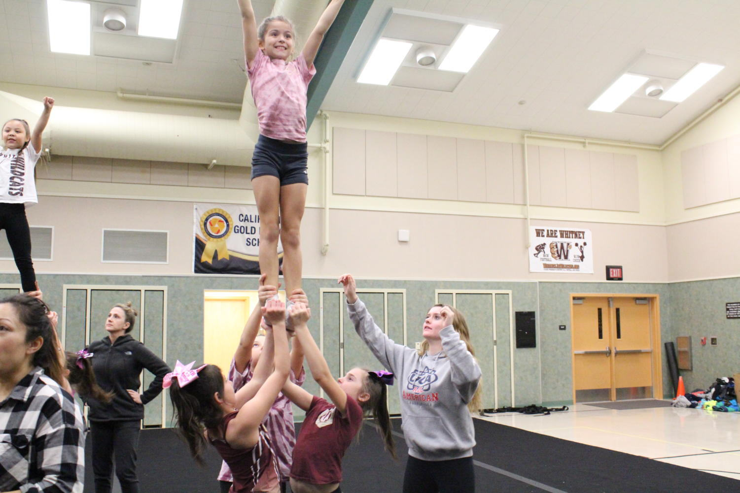 Before running their competition routine full-out, Kylie McLendon helps a stunt group warm up at Whitney Junior Wildcats cheer practice. Photo by Emily Pontes.