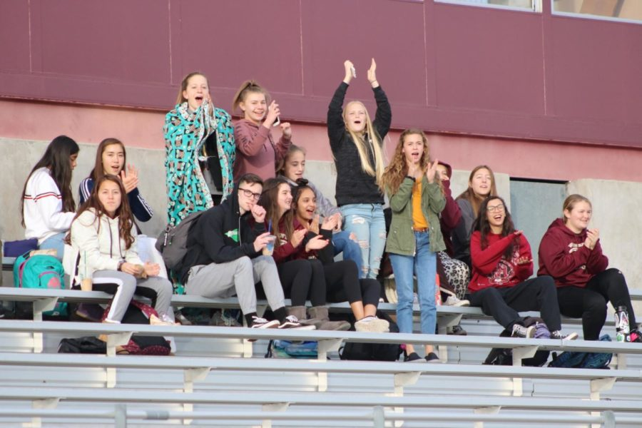 The women's freshman soccer team supports the boys from the stands.