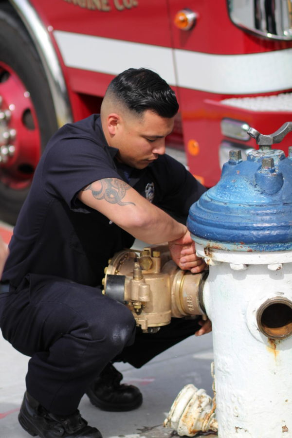 Along the of route sightseeing, a fireman demonstrates the process of changing valves on a fire hydrant to fellow firefighters in training. Photo by Coleton Matics.
