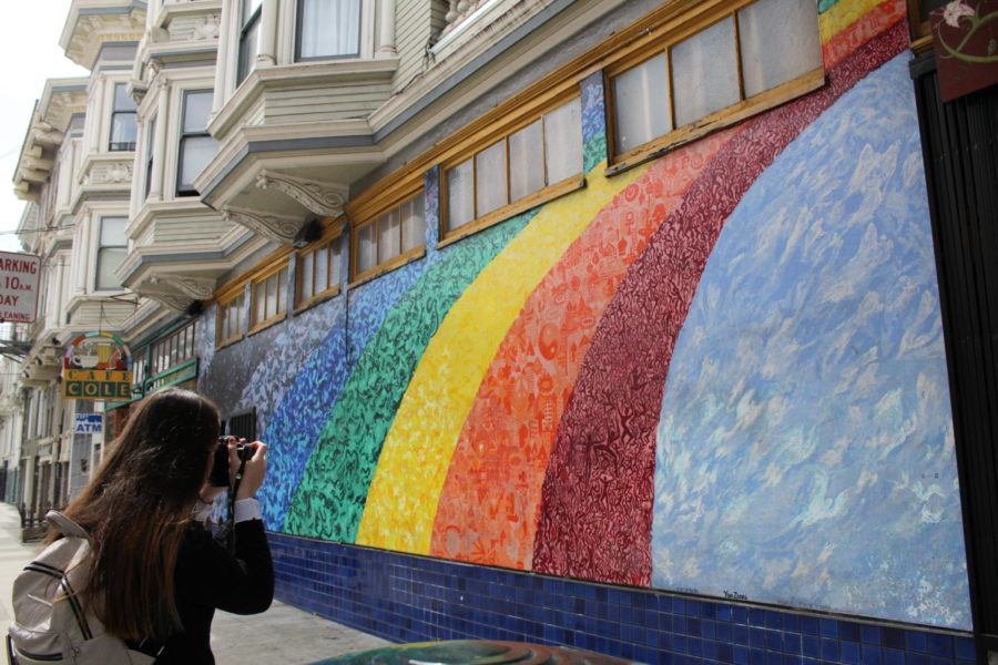 In the Haight-Ashbury district of San Francisco, Kierra Gunn takes a photo of a symbolic mural outside of a historic shop. Photo by Adriana Williams.