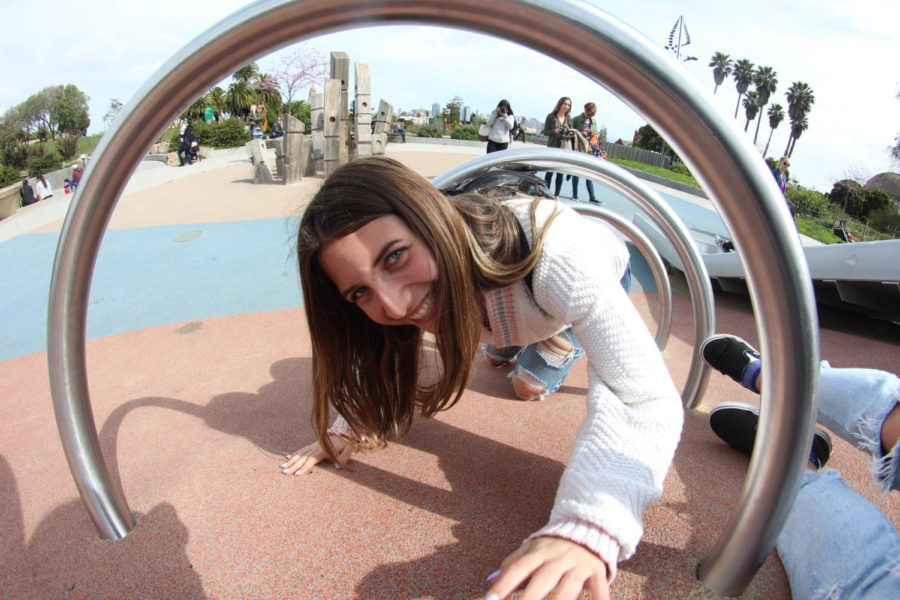After walking 0.2 miles, Emma Accacian crawls through a ring ladder in a playground at Mission Dolores park. Photo by AJ Cabrera.
