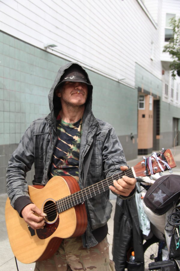 To support himself, a street performer plays his guitar while traveling with his bike. Photo by AJ Cabrera.