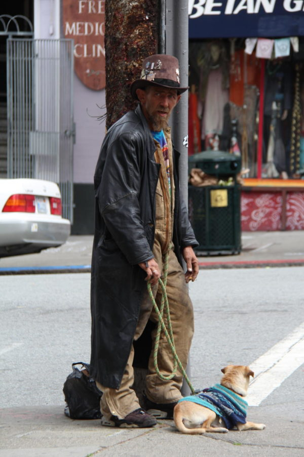 In the Haight, a bystander rests against a pole with his dog. Photo by AJ Cabrera.