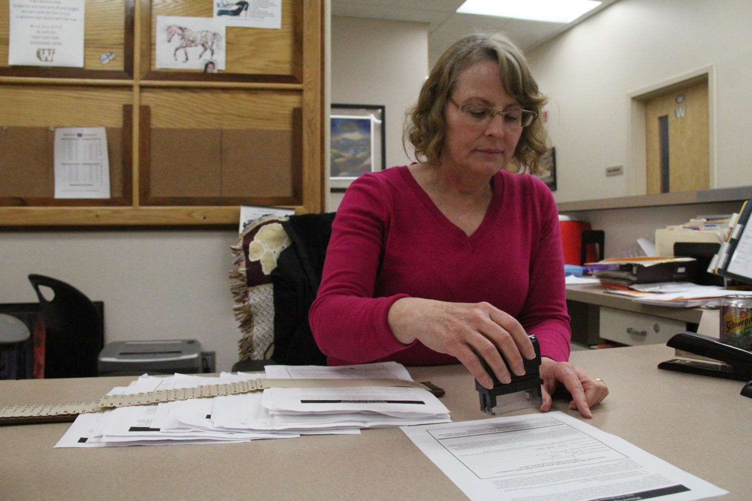 In the front office, Mrs. Pam Cano stamps the Senior Ball agreement form certifying that students do not have any detentions. Photo by Britney Flint.