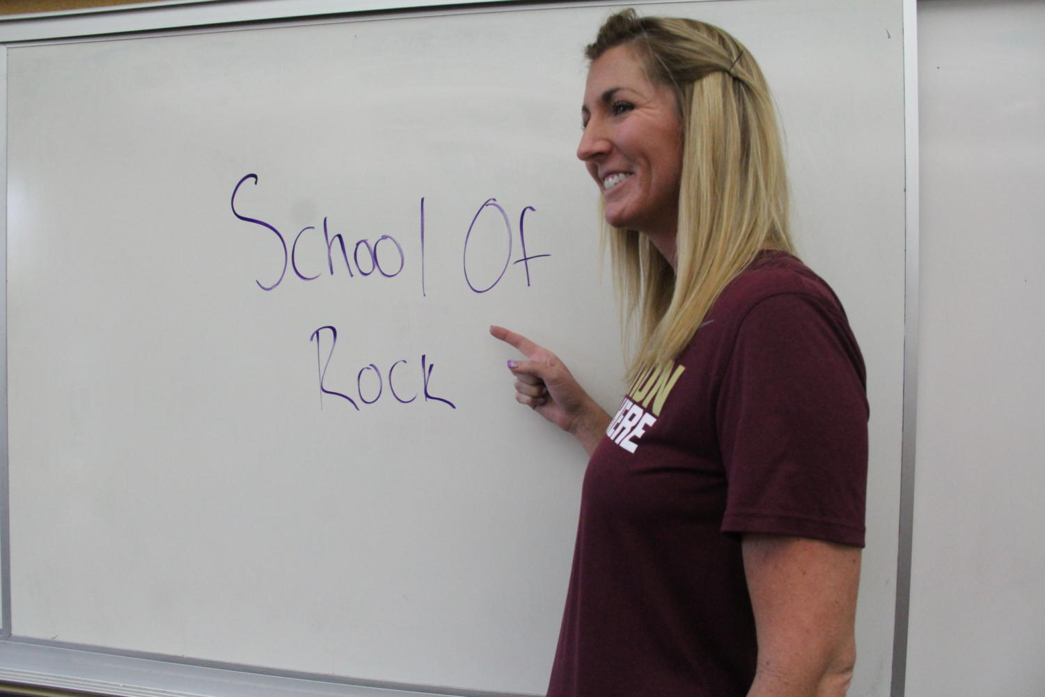 World History and Geography teacher Ms. Suzie Main points to her white board with the words School Of Rock on it. Showing that teachers as well find inspiration from music.
