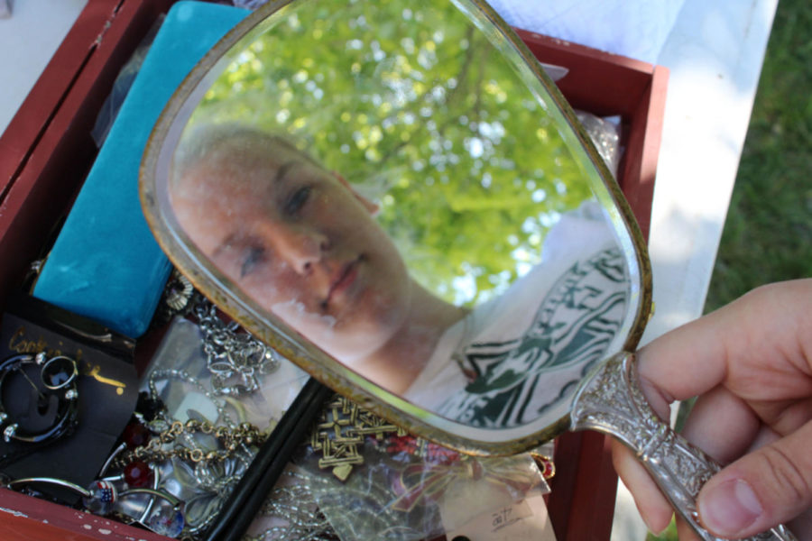 "VISION OF BEAUTY  While shopping at the South Stanford Garage Sale, Mackenzie Scott views her reflection in an antique mirror for sale on April 21. The mirror was in a jewelry box when Mackenzie discovered it, so she had to unlatch the tiny lock on the old jewelry box to get the mirror out before she was able to see herself in the dirty reflexive surface. ""I didn't expect to see such cool antique stuff and was surprised they were giving it away,"" Mackenzie said."