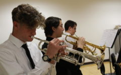 """PRACTICE PAYS OFF. Gavin Fortenberry (left), Daniel Kumpf (center), and Elijah Millington (right) rehearse their songs before their performance at Cuyamaca College on April 21. Fortenberry, Kumpf, and Millington play trumpet in the jazz band. The jazz band received an average score of 90 out of 100 from the judges and finished in second place among others in their category. Fortenberry said, """"[We had] been practicing [the songs] for a few months; I practiced at home and at school. I was tired from the night before [our performance] but I was pumped to play."""""""