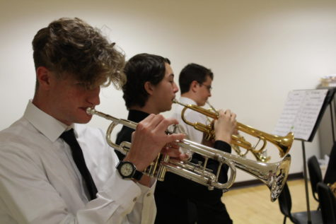 "PRACTICE PAYS OFF. Gavin Fortenberry (left), Daniel Kumpf (center), and Elijah Millington (right) rehearse their songs before their performance at Cuyamaca College on April 21. Fortenberry, Kumpf, and Millington play trumpet in the jazz band. The jazz band received an average score of 90 out of 100 from the judges and finished in second place among others in their category. Fortenberry said, ""[We had] been practicing [the songs] for a few months; I practiced at home and at school. I was tired from the night before [our performance] but I was pumped to play."""